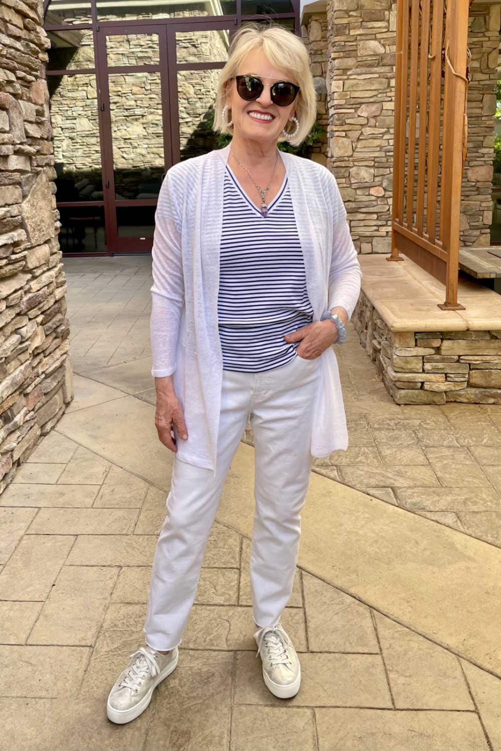 blonde woman wearing white sweater, white jeans and gold sneakers in patio