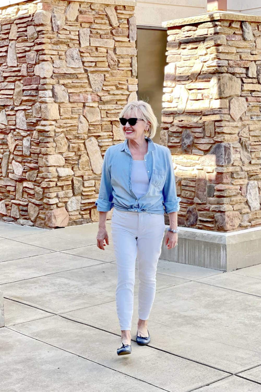 woman walking toward to wearing chambray shirt white jeans and blue shoes
