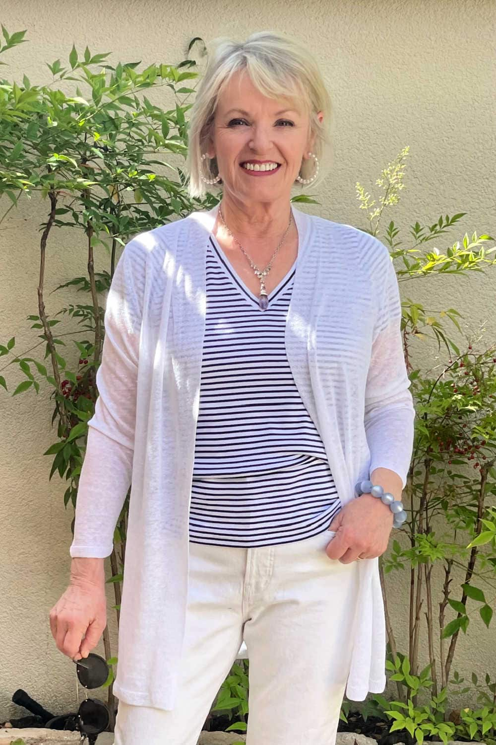 blonde woman wearing striped tee and white line sweater in courtyard garden