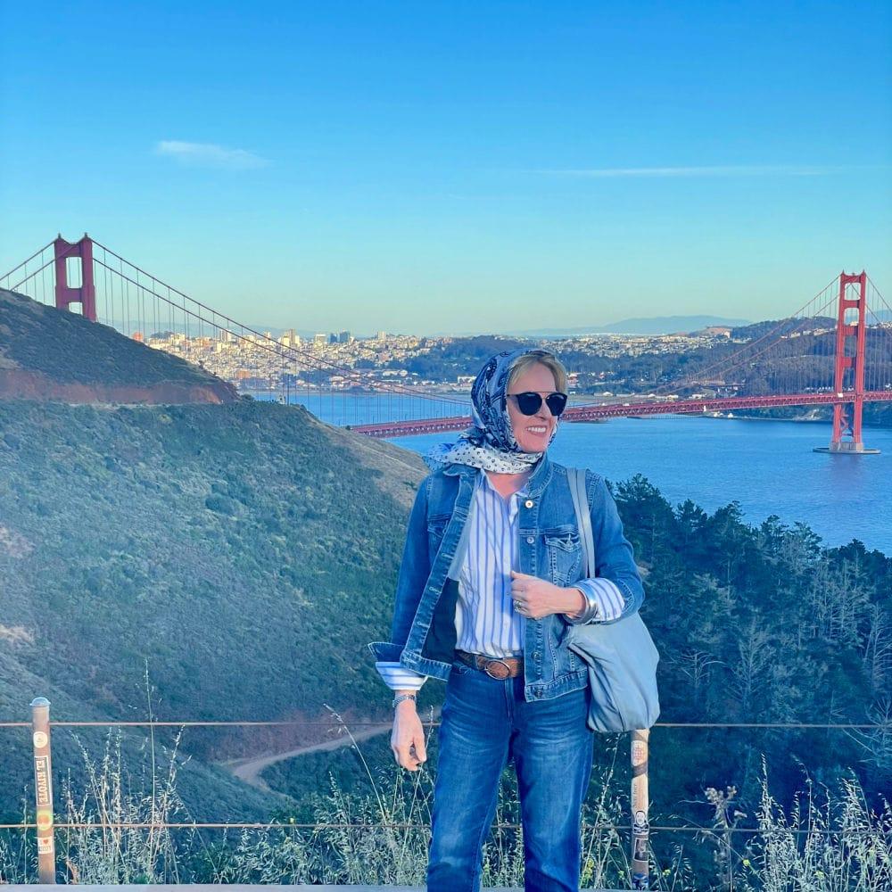 woman standing on bluff above the goldken gate bridge wearign denim jacket and jeans