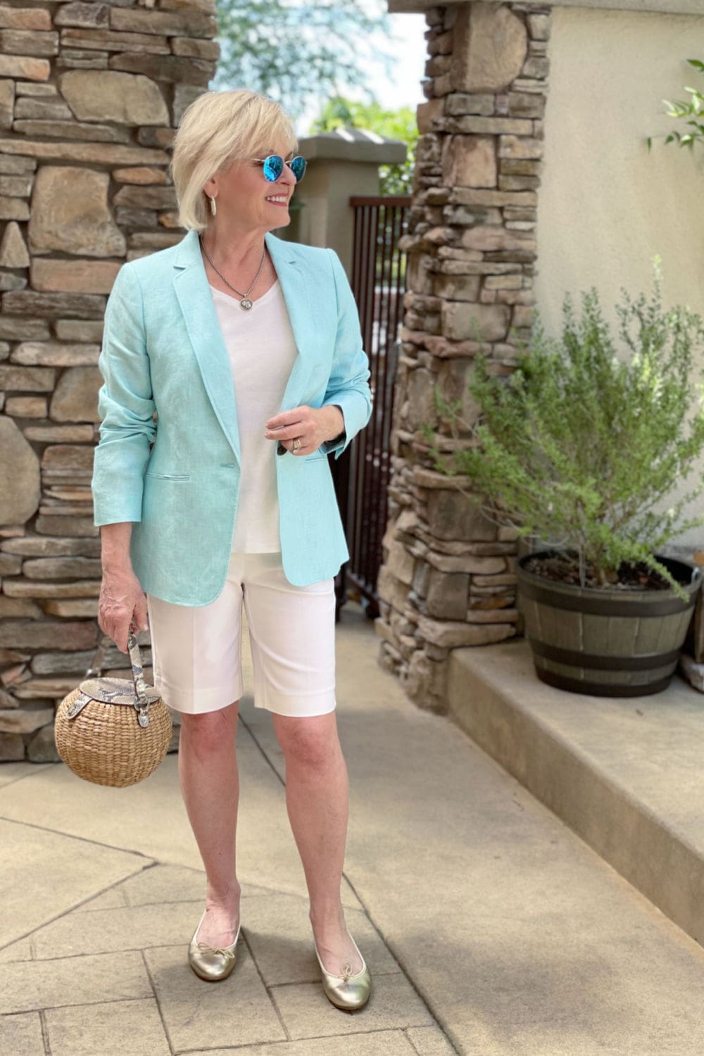 blonde woman wearing a blazer with shorts outfit plus metallic shoes
