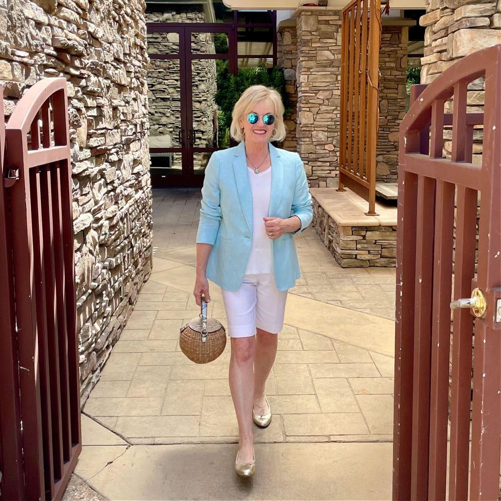 woman walking through gate wearing aqua blazer