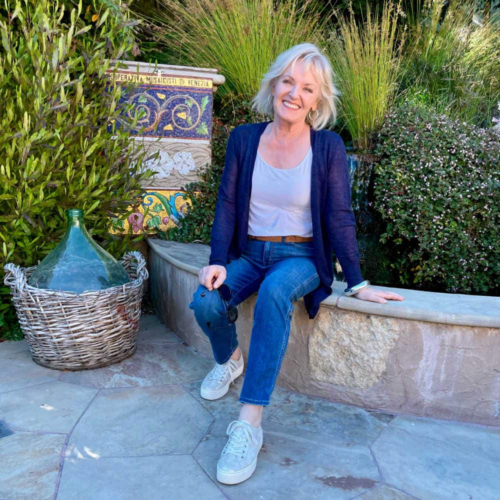 over fifty blogger jennifer connolly sitting on wall wearing blue cardrigan and blue jeans
