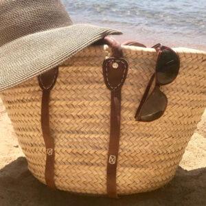 beach bag sunglasses and sunhat on beach
