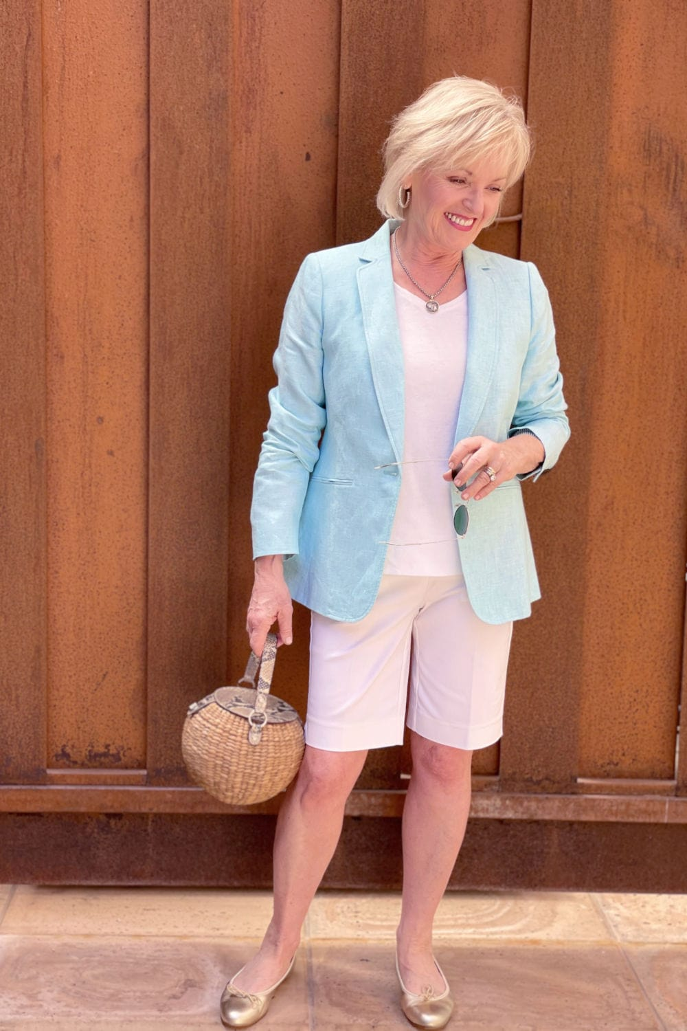 woman standing in front of fence wearing linen blazer with shorts with gold ballet flats