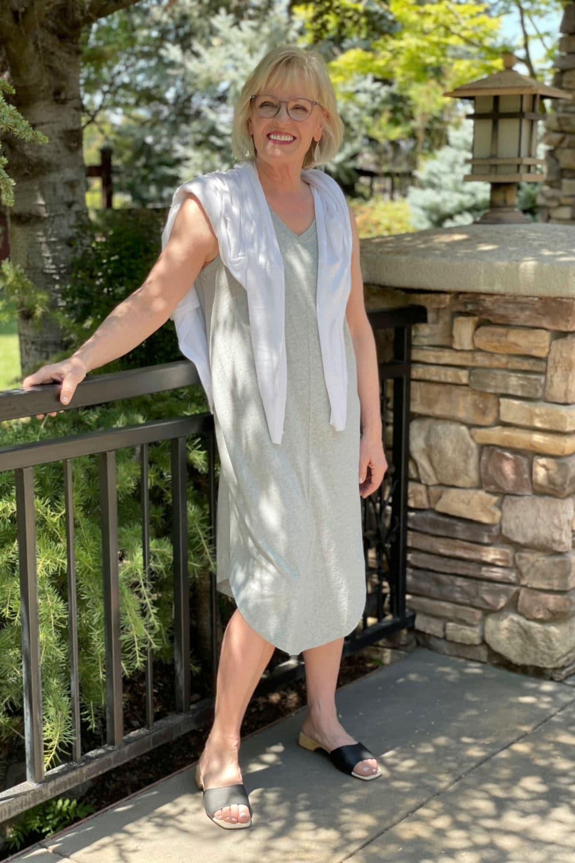 blonde woman wearing gray sleeveless dress and white sweater