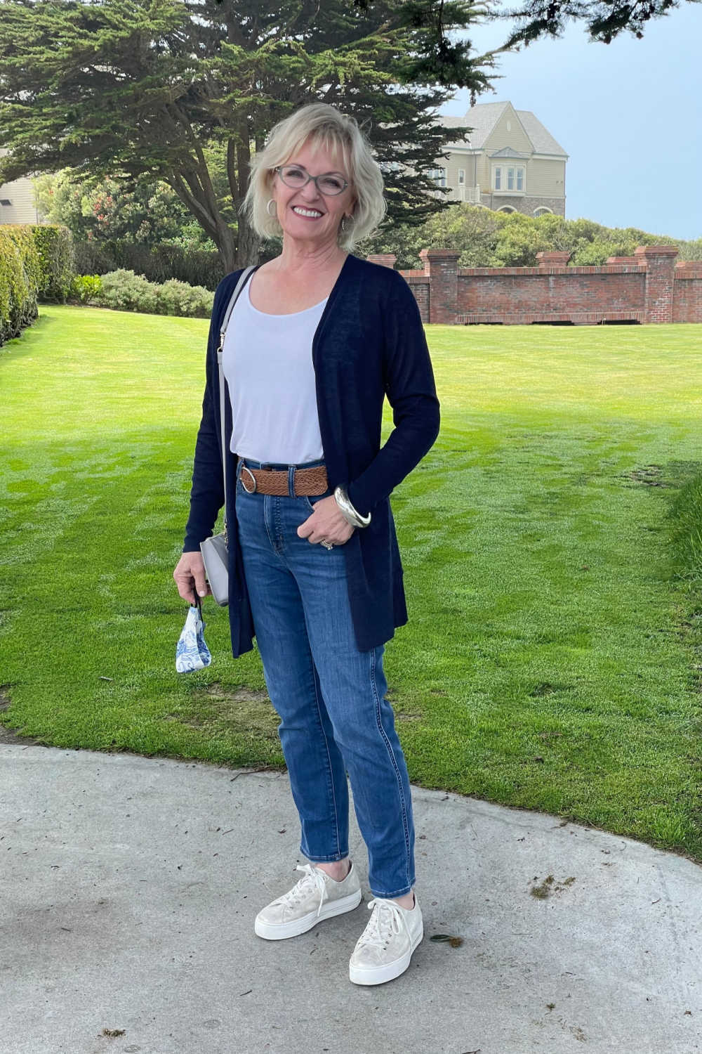 woman standing in jeans and blue sweater in front of lawn and hotel at half moon bay