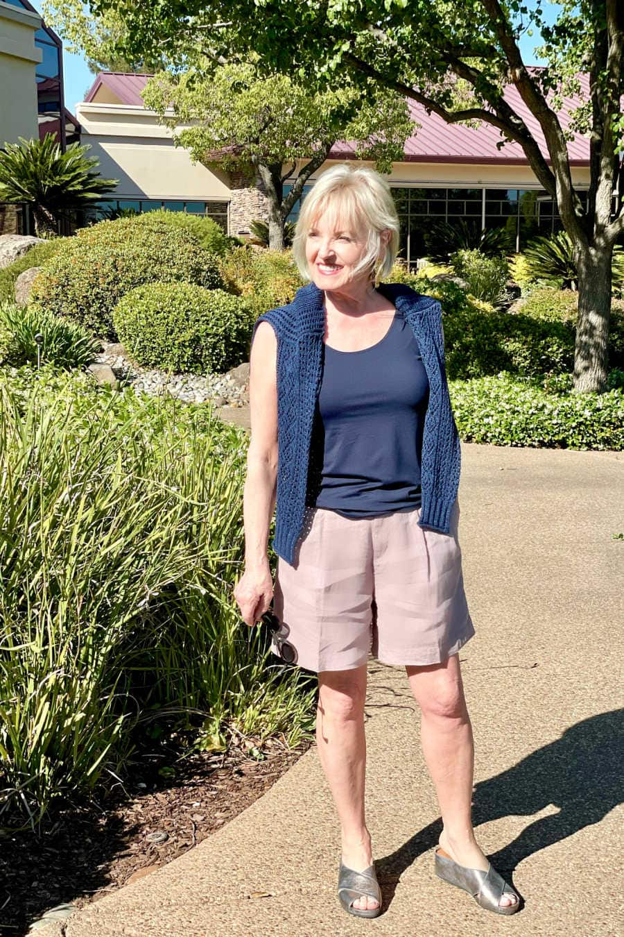 woman standing in sun with sweater over shoulders, wearing line shorts and metallic sandals