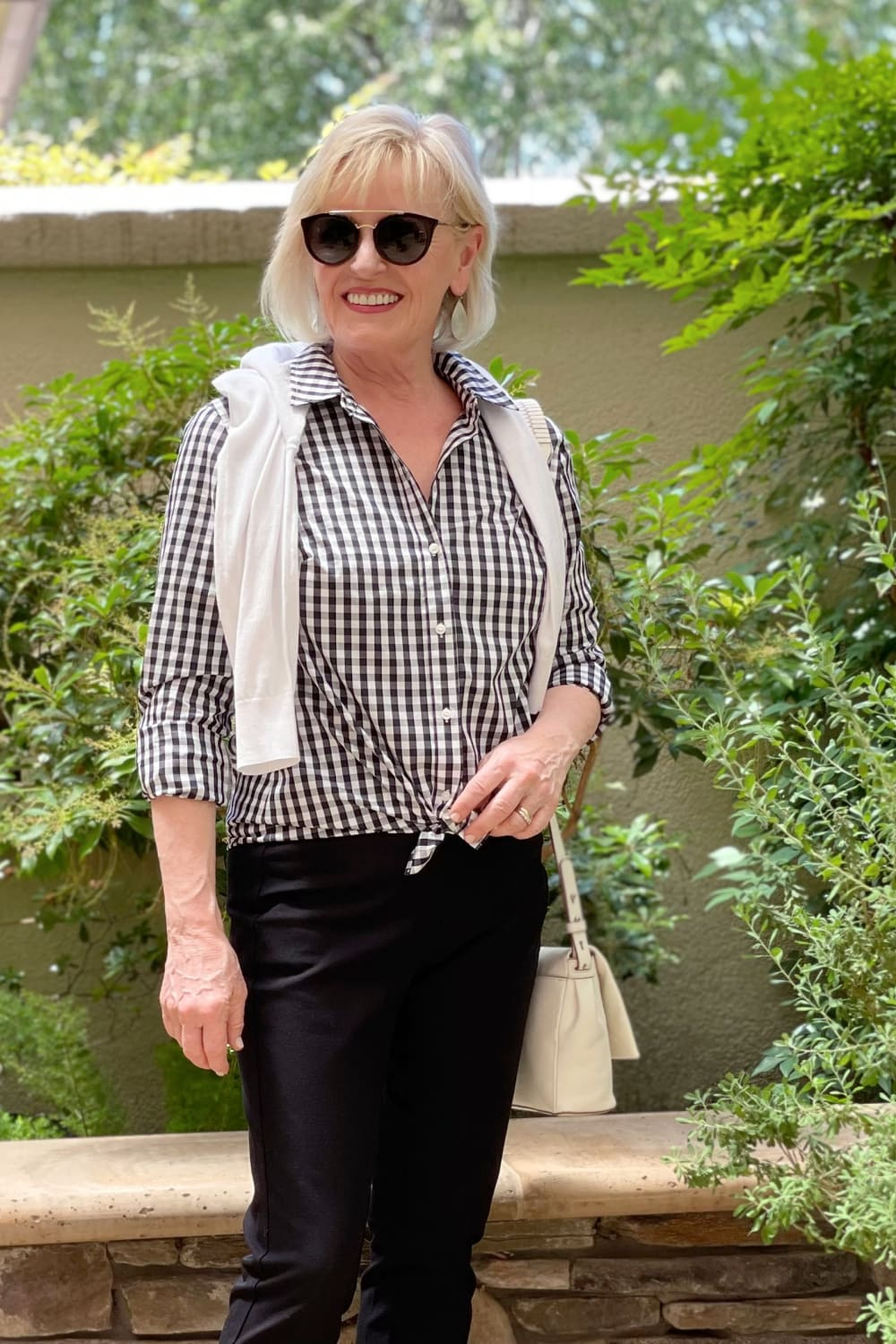 woman wearign black and nwhite gingham shirt and black sunglasses