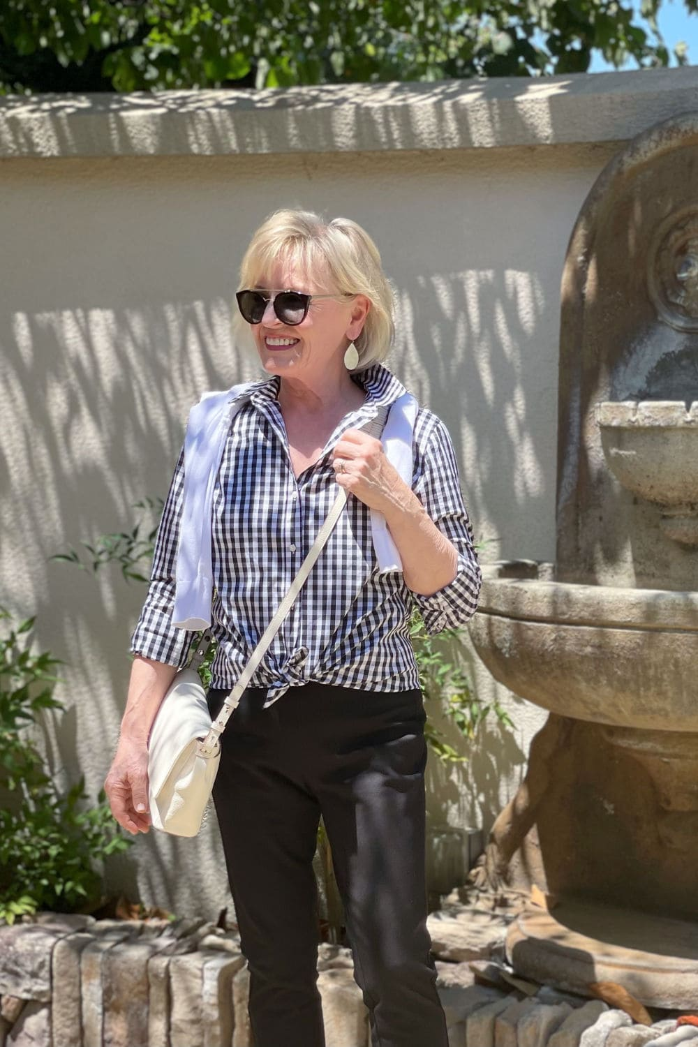 blone woman standing in front of wall fountain wearing gingham shirt