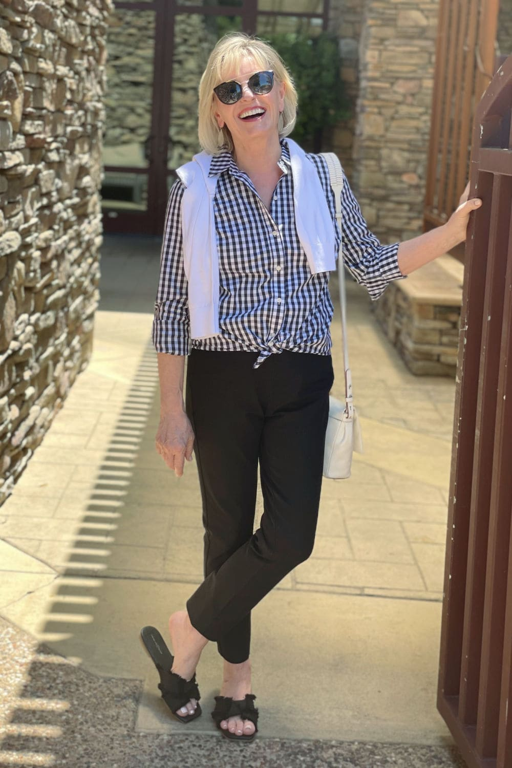 woman smiling into camera with gingham shirt and black pants