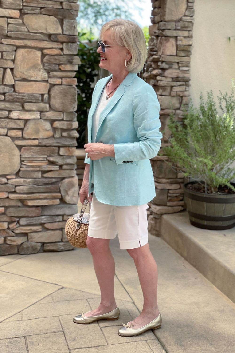 sideways view of blonde woman wearing aqua blazer with gold shoes