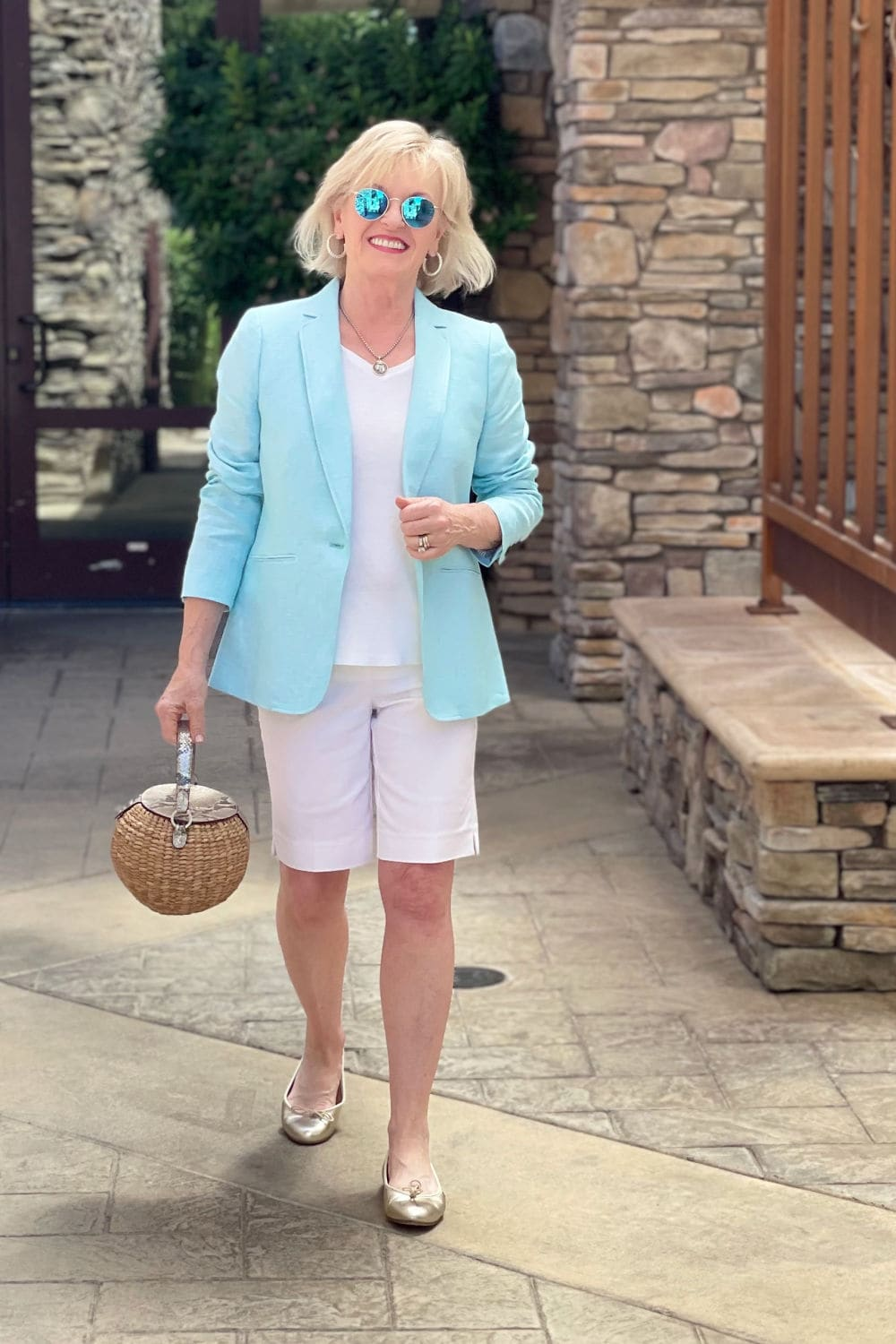 over 50 blogger walking toward the camera in linen blazer, gold flats and white shorts