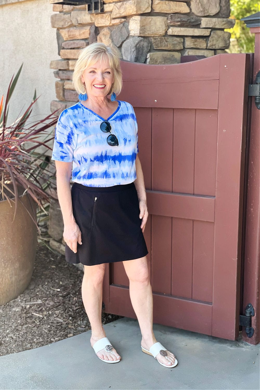 jennifer connolly of a well styled life weaing blue tee and black skort with white sandals