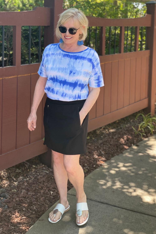 blonde woman walking next to fence wearing tye dye tee and casual skort