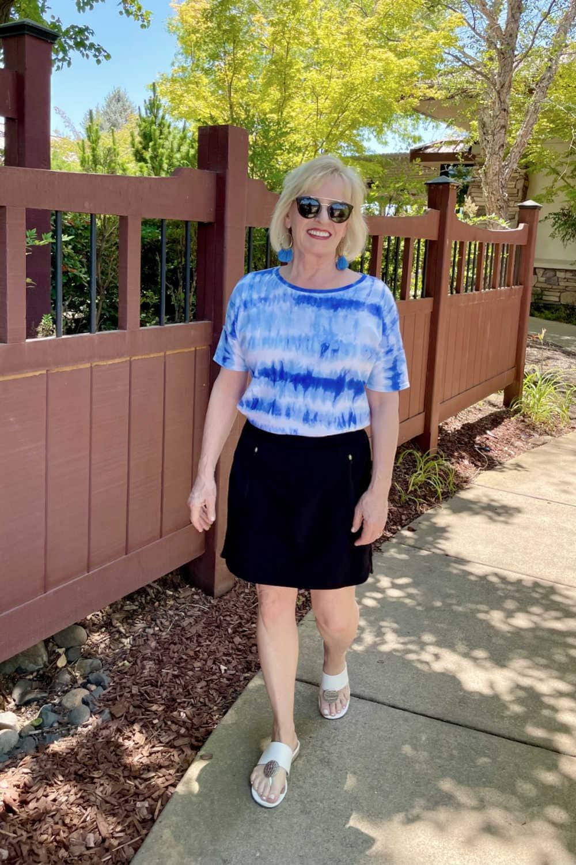 woman walking beside fence wearing black skorts