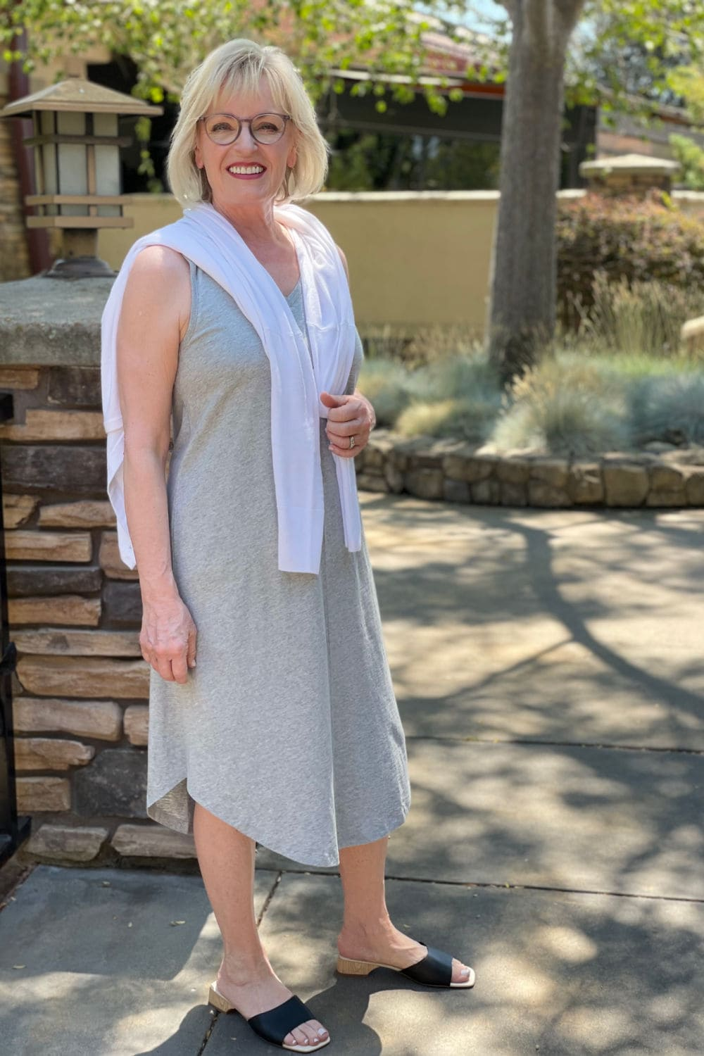 woman wearing gray dress and white sweater with no sleeves