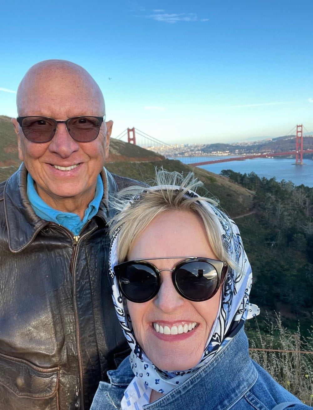 man an woman smiling into camera with golden gate bridge behind them