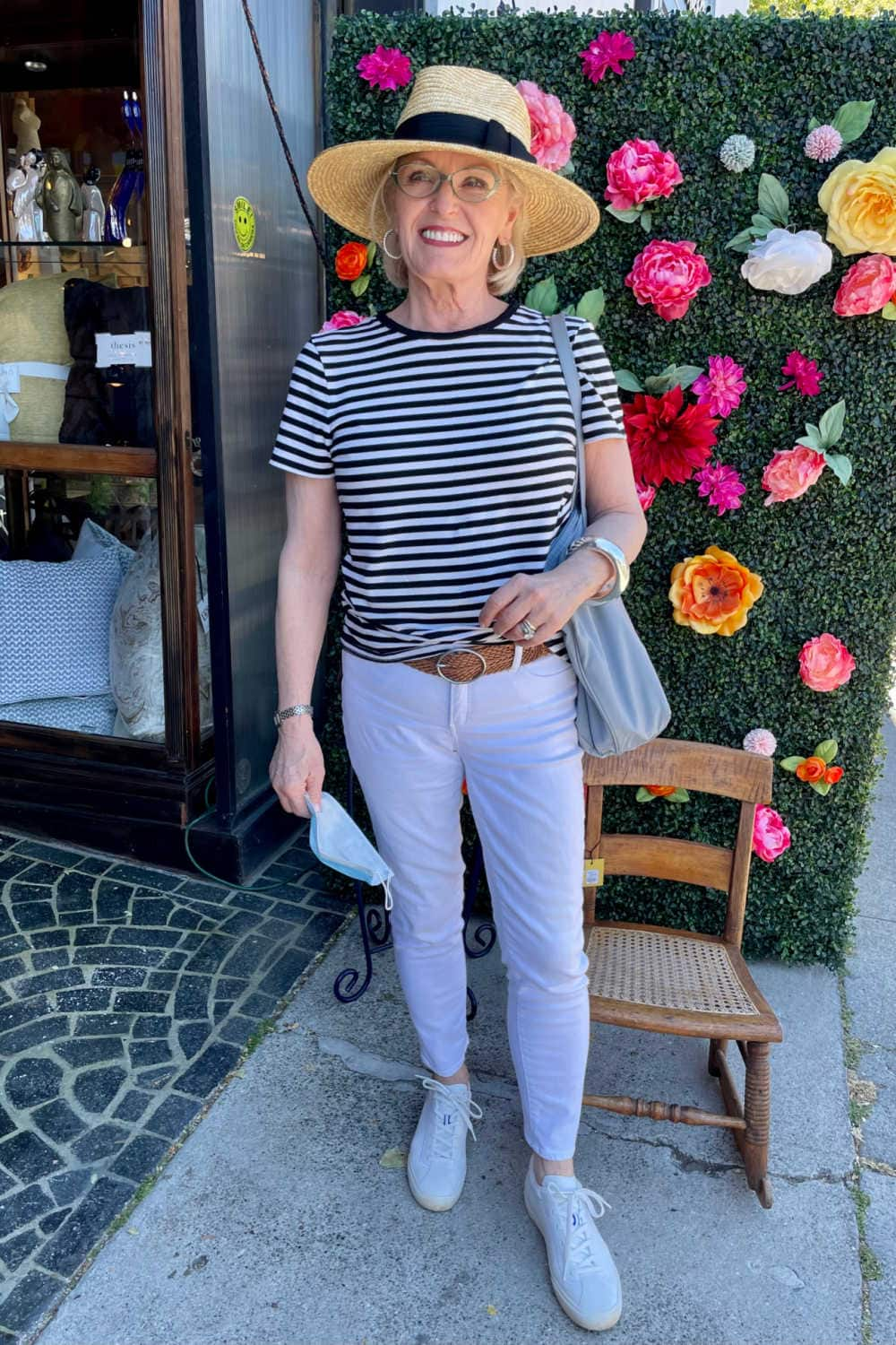 woman wearing whote jeans and strippped tee in front of flower store