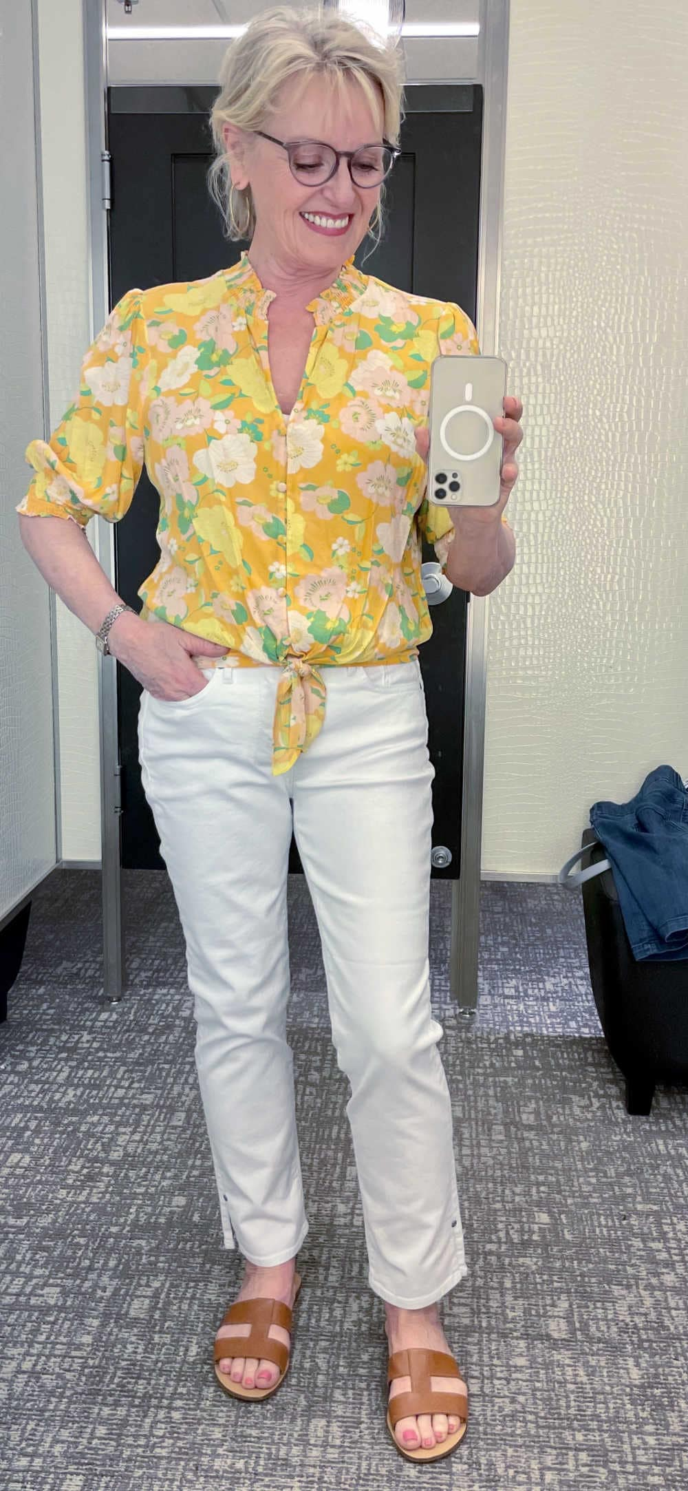 blonde woman in selfie wearing yellow top and white jeans