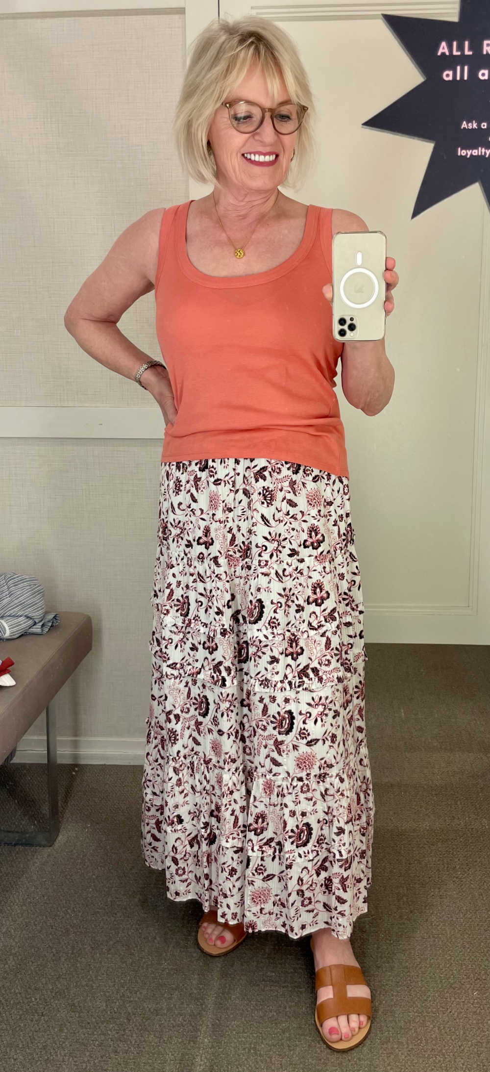 woman wearing orange tank and skirt in loft dressing room
