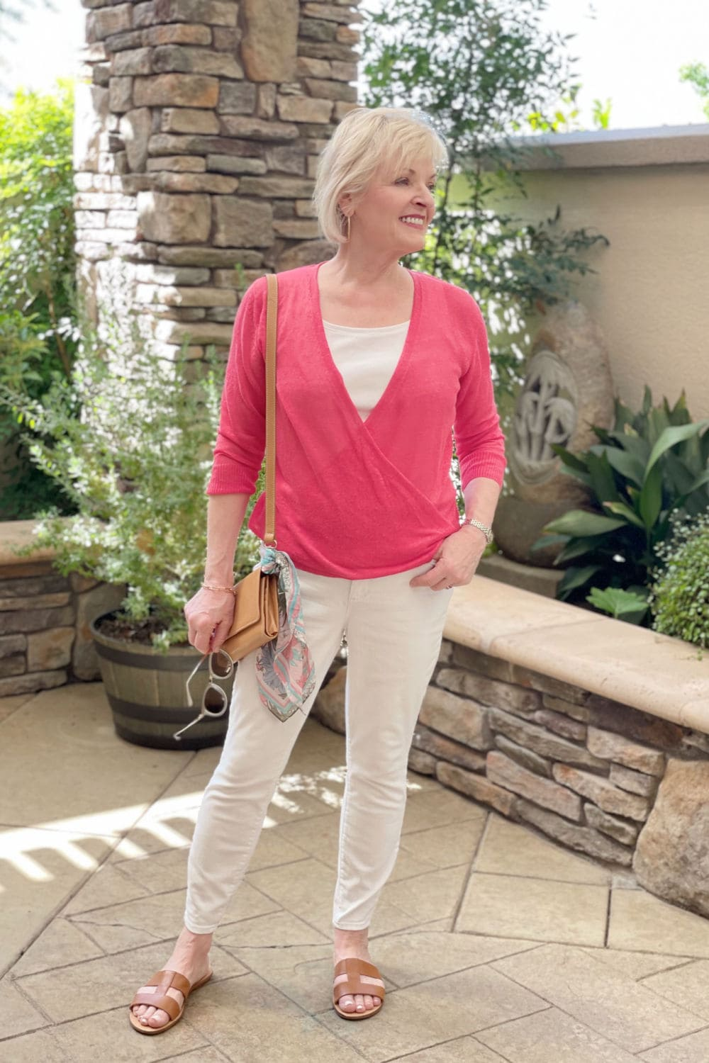 blonde woman wearing white jeans and top with red sweater