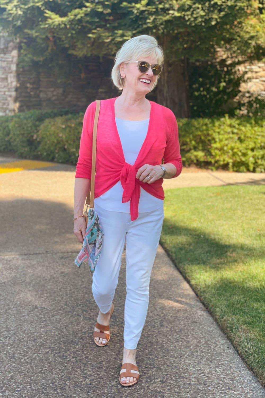 woman walking toward camera wearing white jeans and pink cardigan