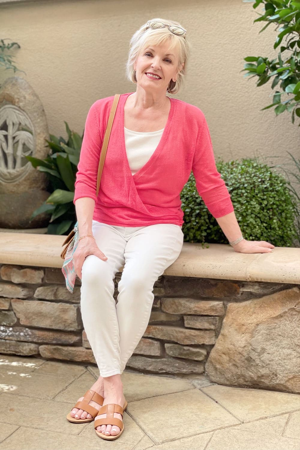 blonde woman sitting on wall wearing white jeans and tee with red sweater