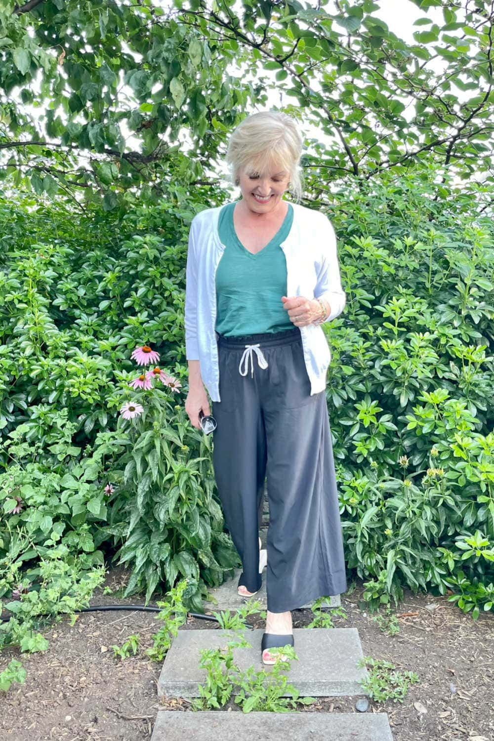 over 50 blogger jennifer connolly walking in garden wearing wide legged Zella pants with white cardigan