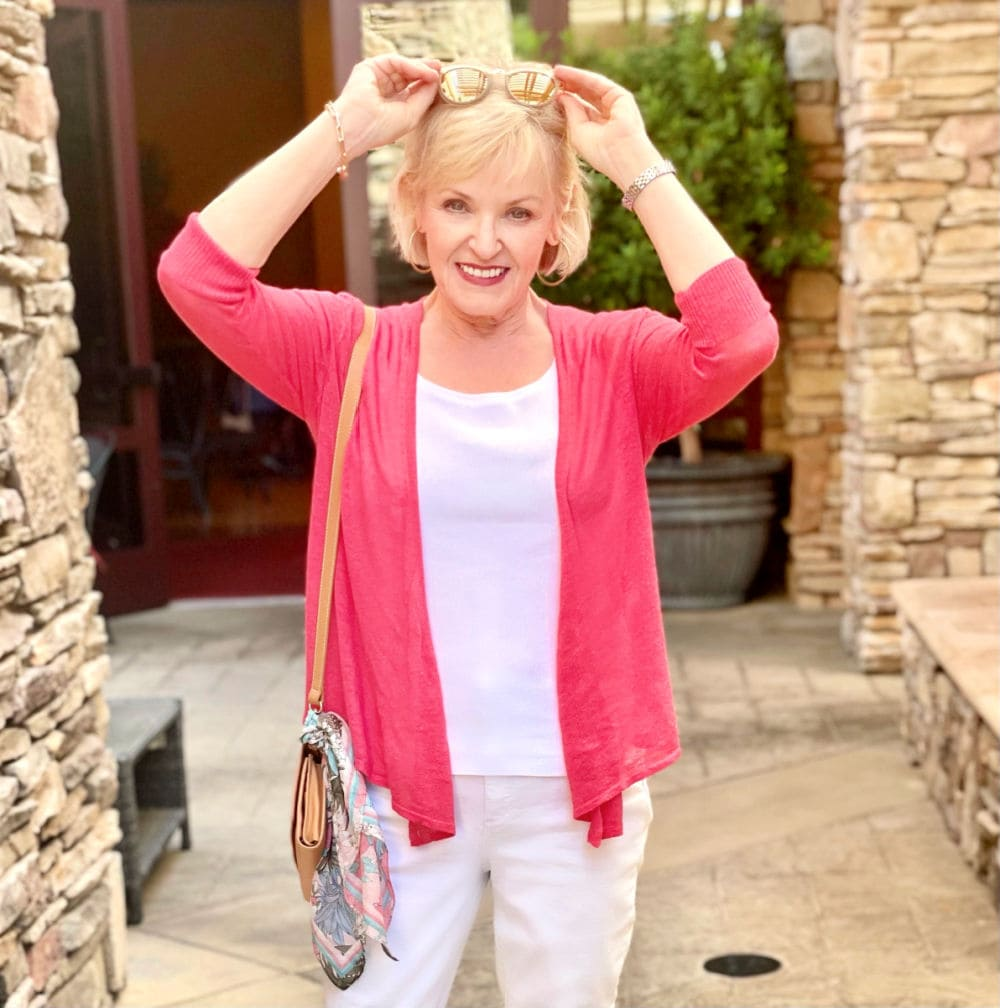 over 50 fashion blogger wearing pink sweater over white tank top