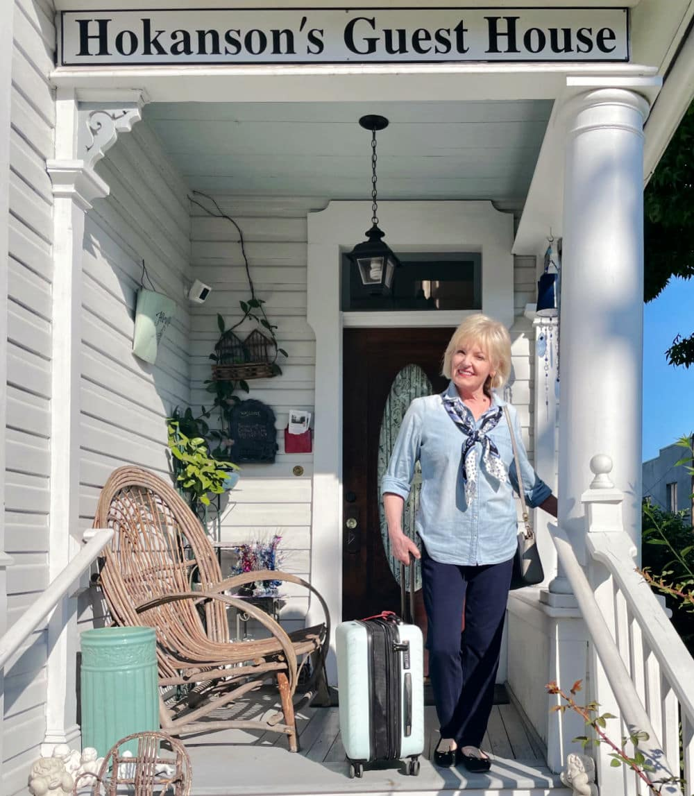 woman on porch of bed and breakfast with luggage