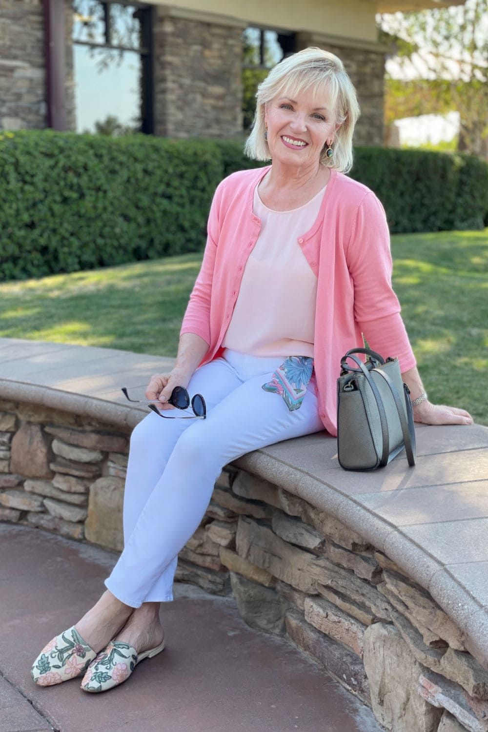 over 50 blogger sitting on wall in white jeans and pink cardigan