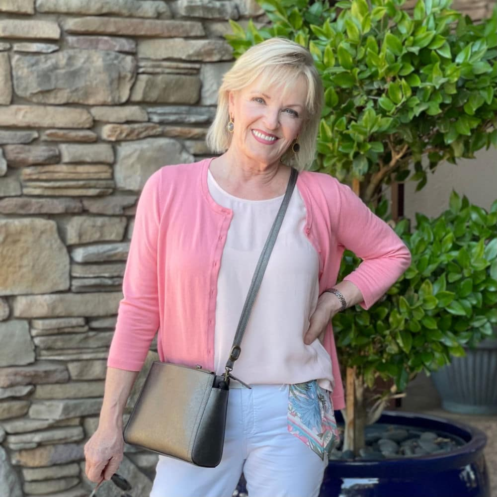 blonde woman wearing pink cardigan, pibnk tanks and carrying a crossbody