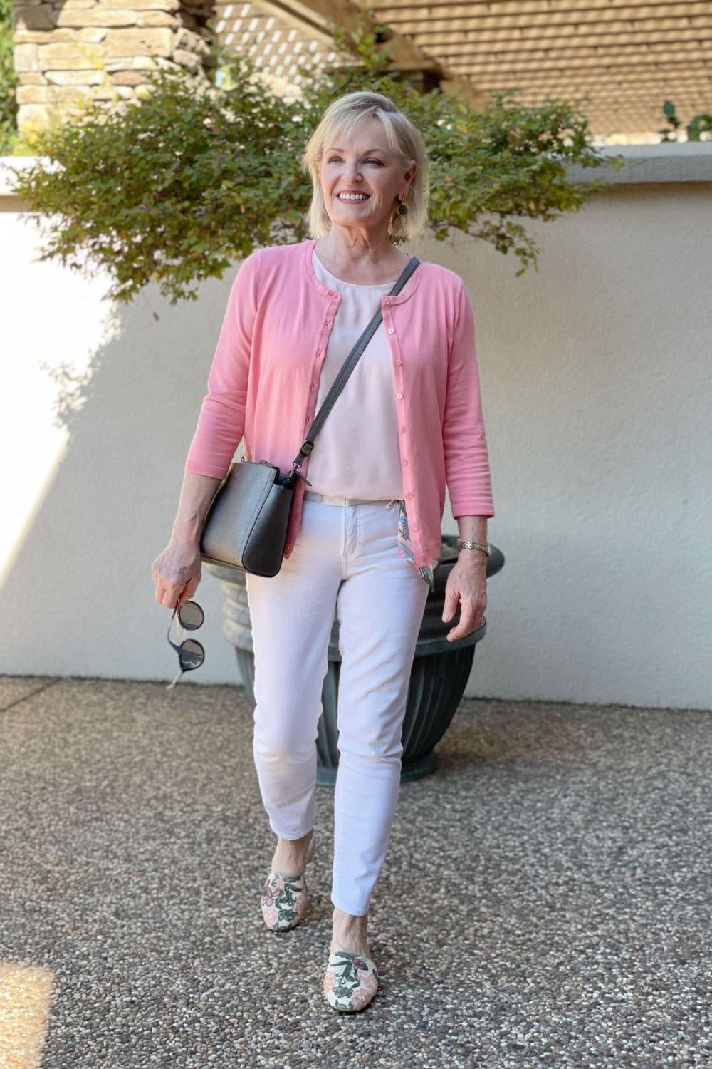 woman walking toward camera wearing salmon colored sweater and white jeans with embroidered mules