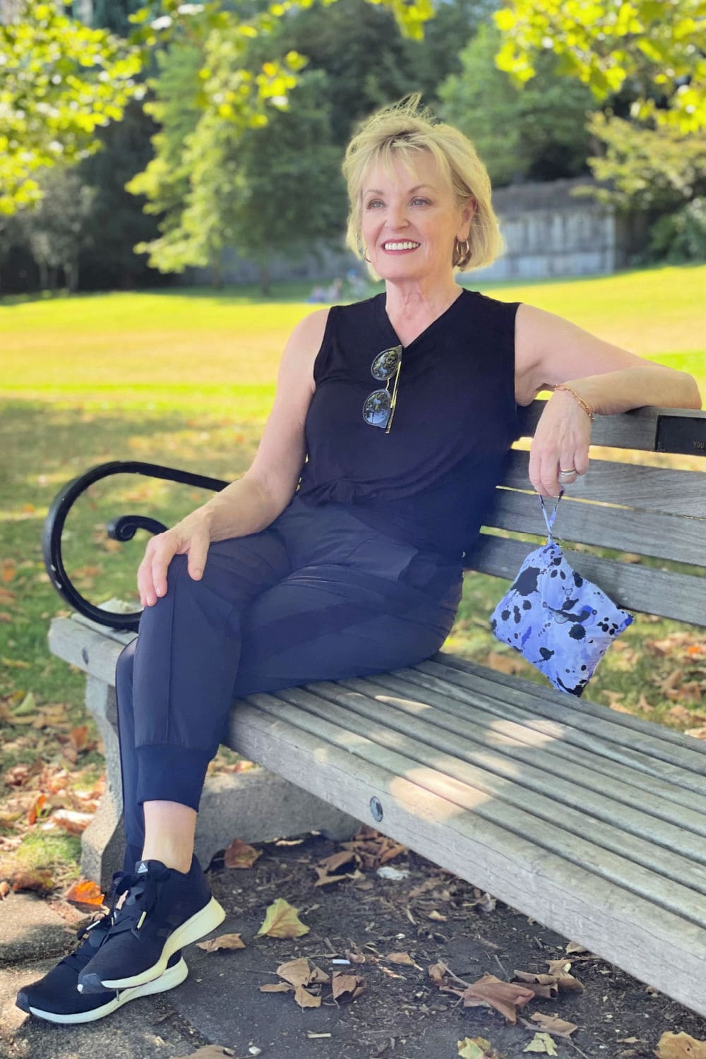 woman sitting on bench wearing black Zella pants and top