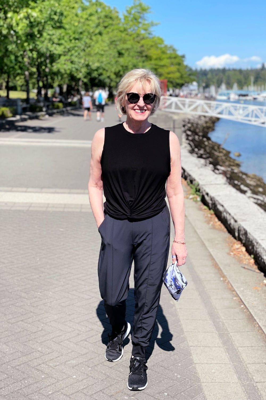 blond woman walking along sea wall with hand on pocket of Zella pants