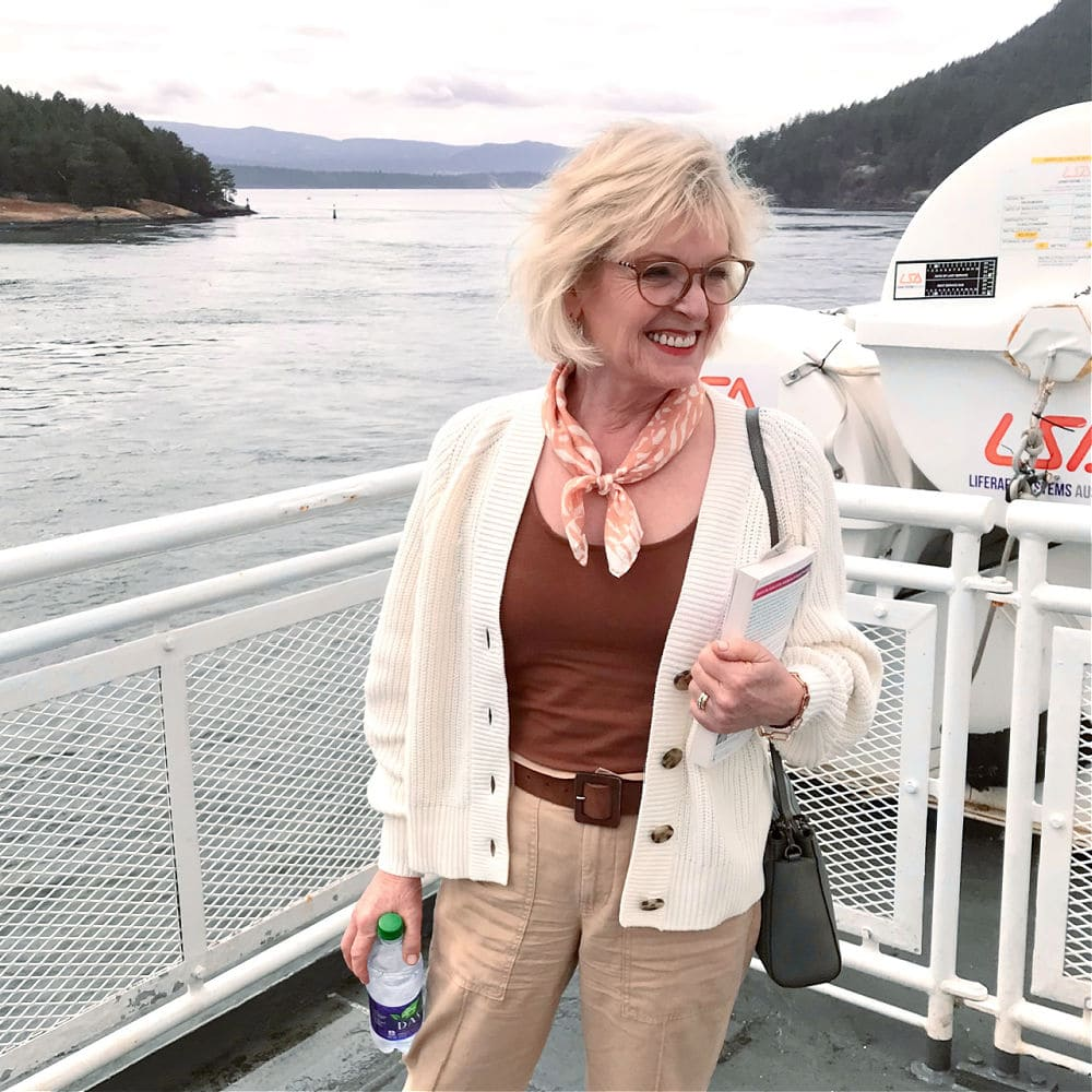 over 50 woman wearing shrunken sweater and cinnamon colored tank top on deck of ferry