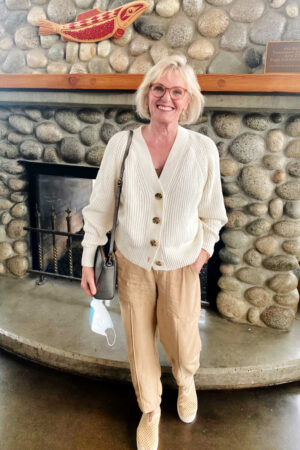 over 50 blogger wearing ivory sweater and cargo pants in front of rock fireplace