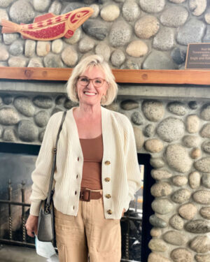 woman infrotn of rock fireplace wearing ivory sweater and tank top