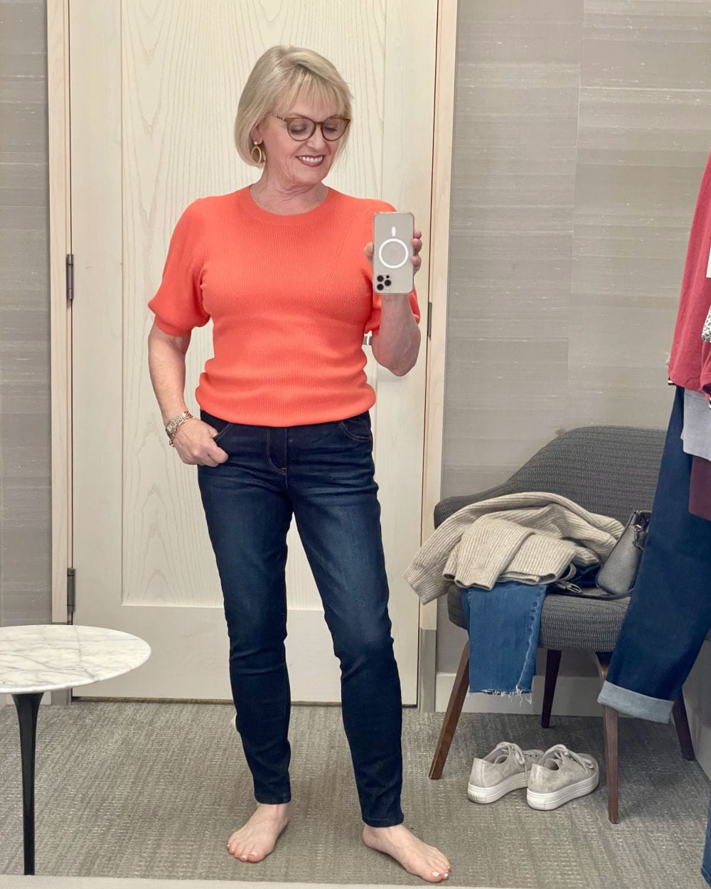 woman wearing coral sweater and skinny jeans on Nordstrom dressing room