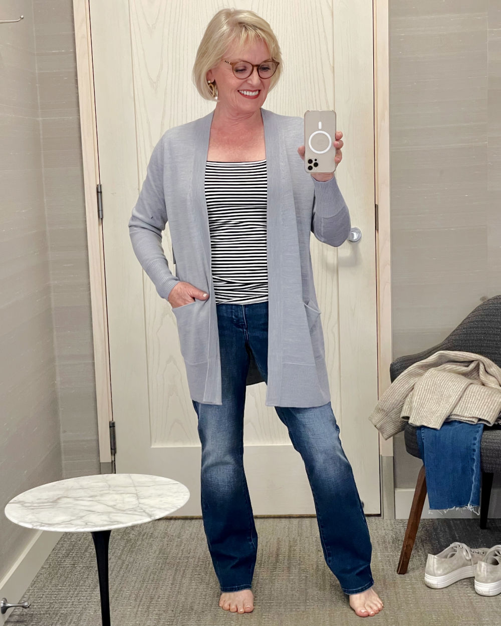woman taking selfie in dressing room wearing gray cargican striped tee and straight jeans