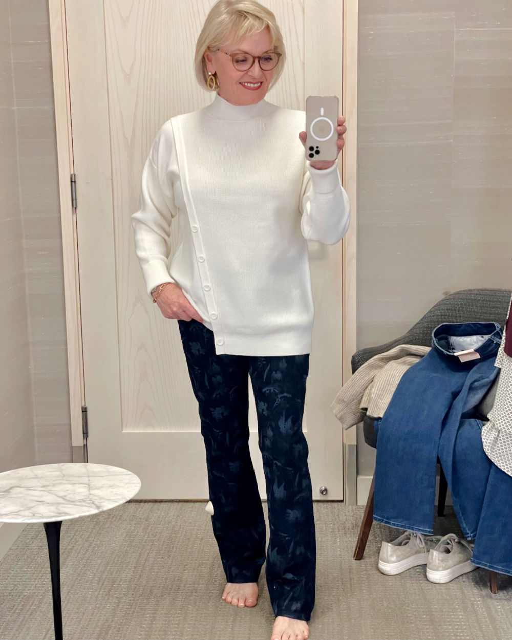 woman wearing ivory sweater and patterned jeans in Nordstrom dressing room