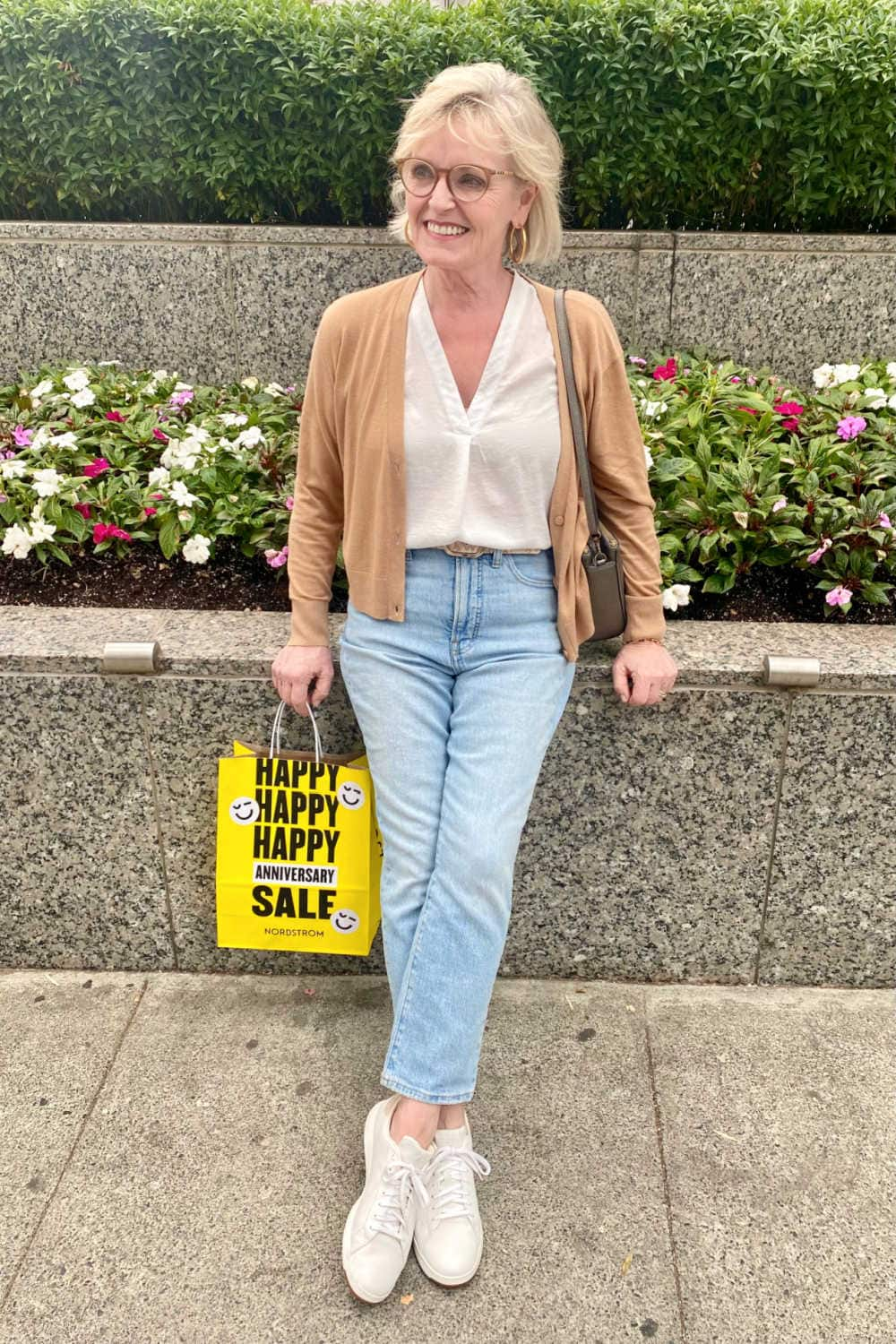 blonde woman wearing camel colored cardigan, blue jeans, metallic sneakers leaning against planter