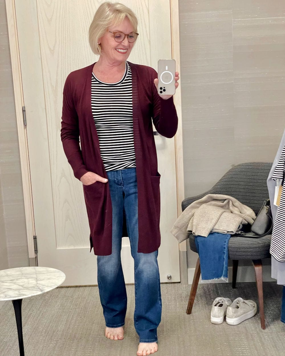 woman wearing wine colored cardigan and blue jeans