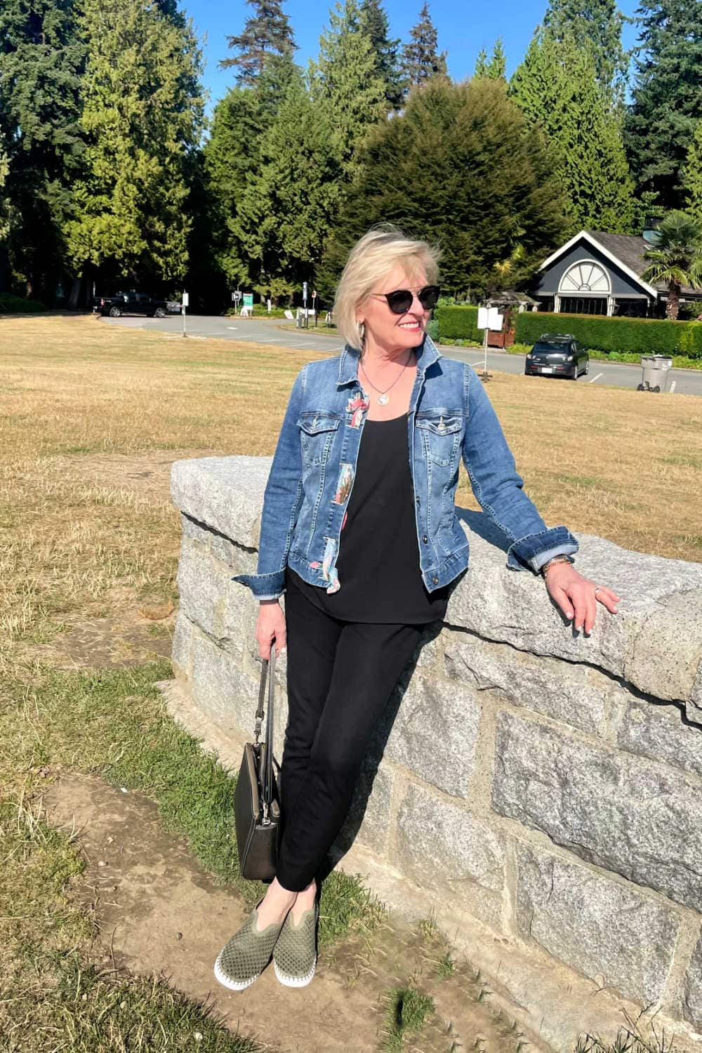 blonde woman wearing black outfit with denim jacket