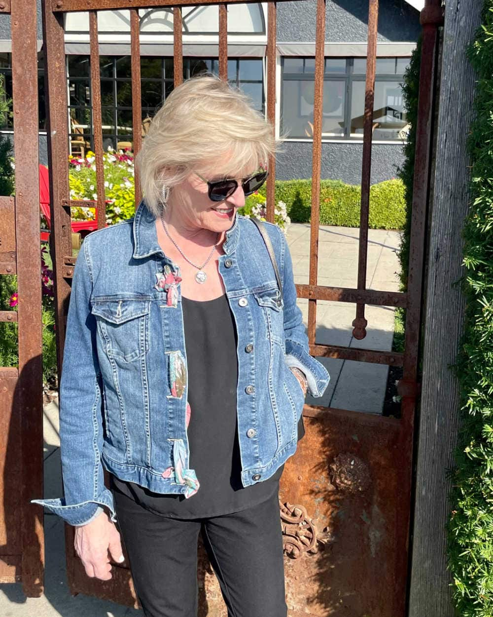 Woman in front of iron gate wearing denim jacket with scarf woven through button holes