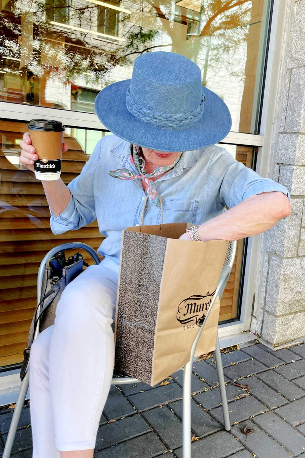 woman holding coffee cup lookin gin her Murchie's shopping bag