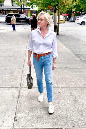 woamn walking down sgtrett in white shirt and jeans carrying bronze handbag