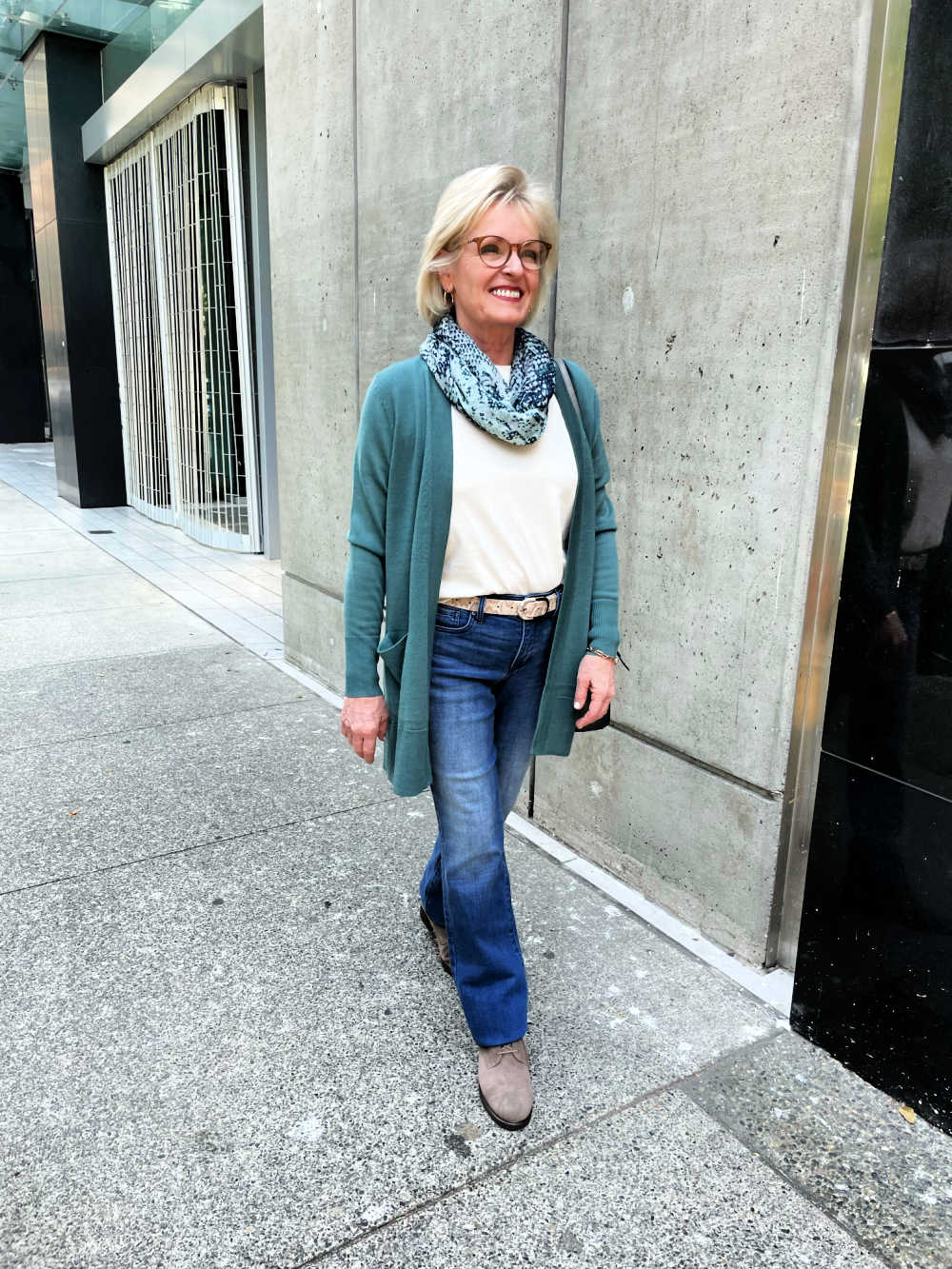 woman walking on strett wearing green cardigan, white tee, and jeans