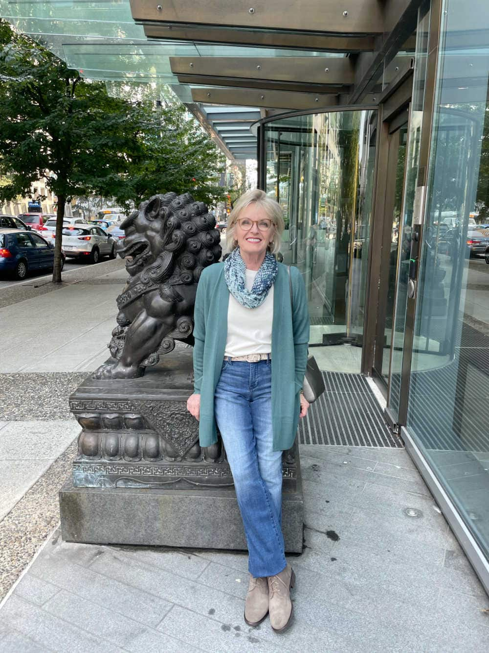 woman leaning against statue wearing green sweater and blue jeans and taupe suede boots